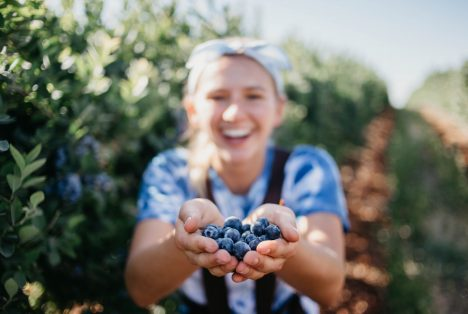 A képen egy vegán lány gyümölcsökkel látható.